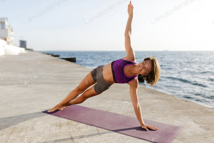 Happy woman leaning on her hand while training yoga poses by the sea