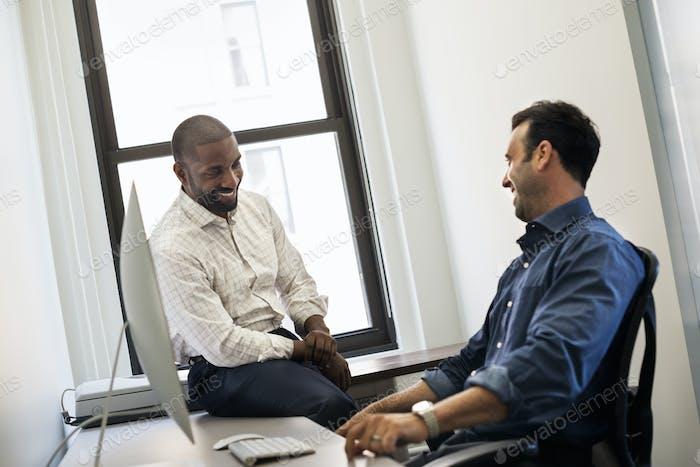 Büroleben, Mann lehnt sich zurück in einem Bürostuhl im Gespräch mit einem Kollegen