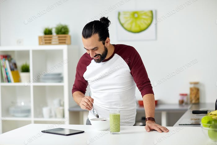 man with tablet pc eating breakfast at home