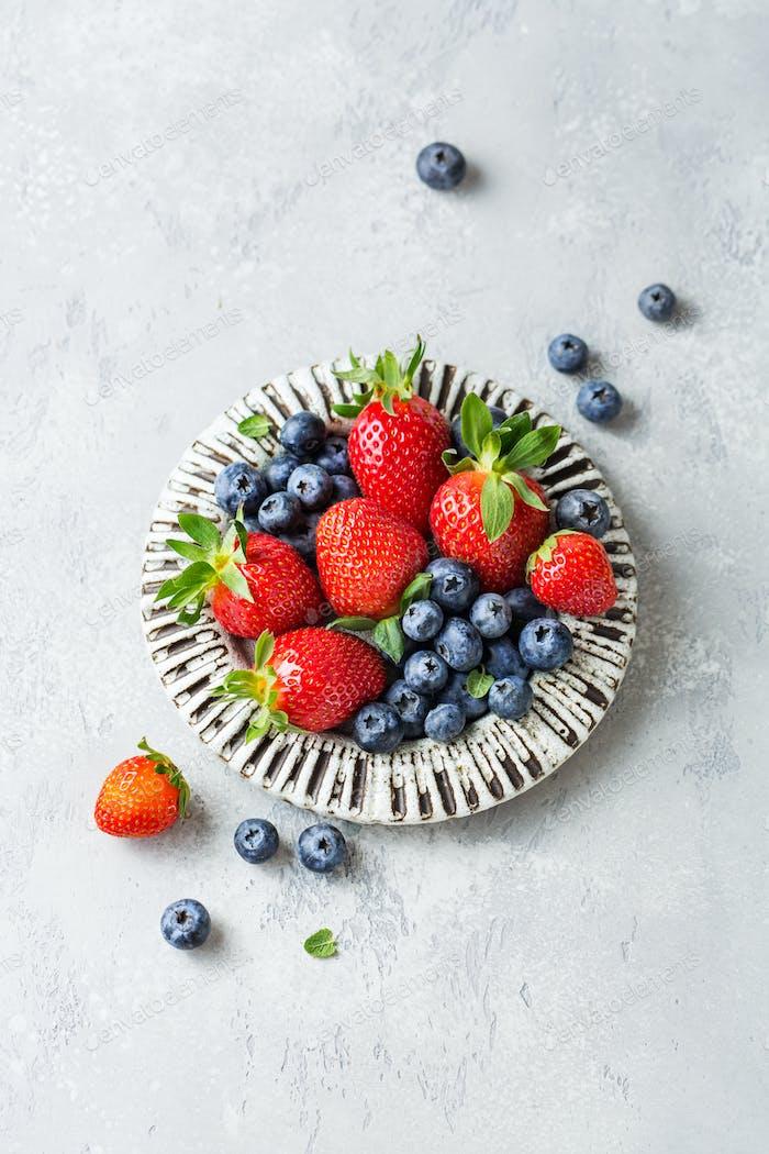 Erdbeeren und Heidelbeeren in einer Keramikplatte