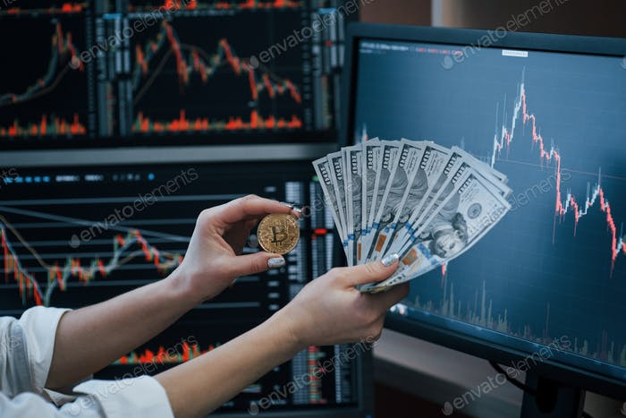 Woman's nd man's hand holding bitcoin and money in modern office with many monitors with graphs