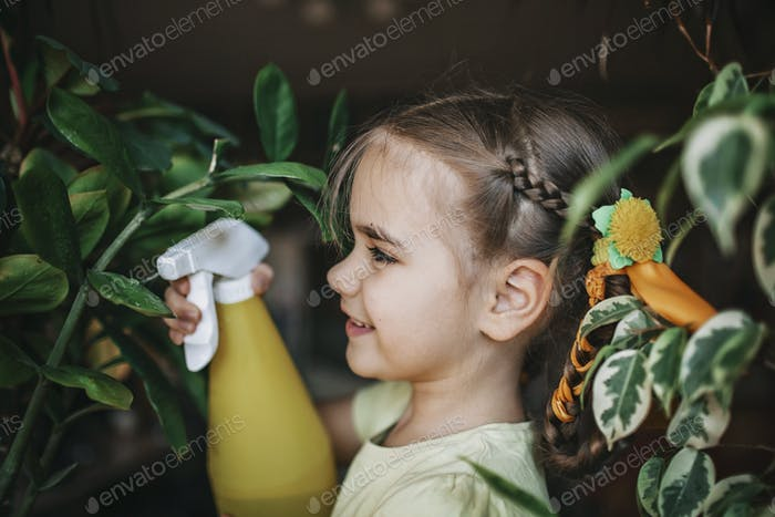 Cute girl helping to care for home plants on the window, plant parents concept