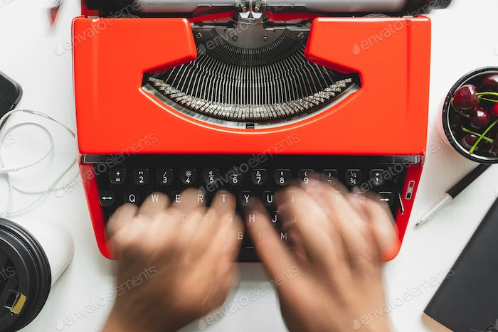 Man hand working with bright red vintage typewriter