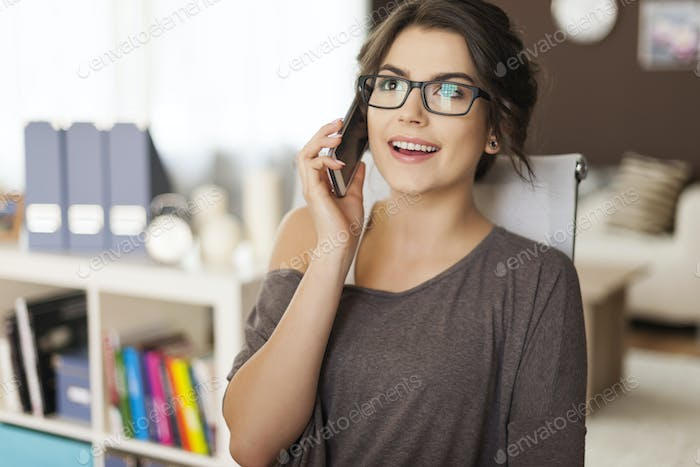 Beautiful woman sitting on chair and talking by smartphone