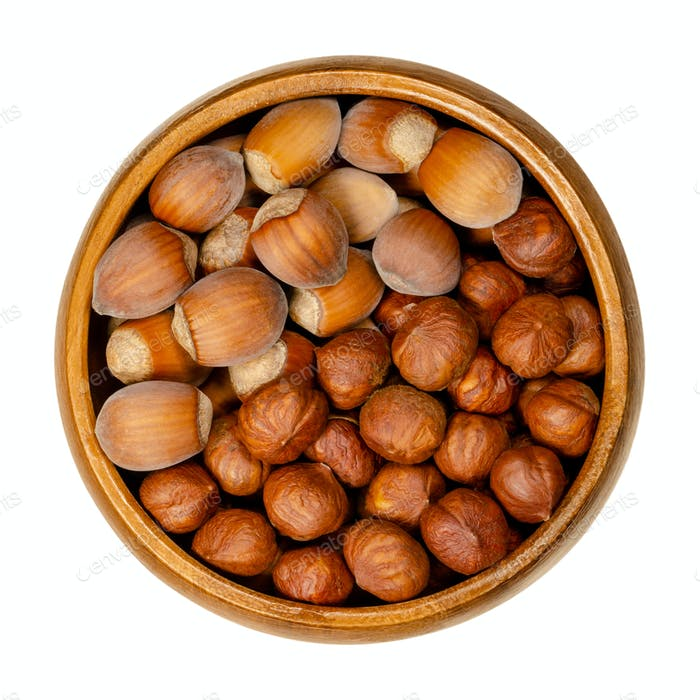 Shelled and unshelled hazelnuts in a wooden bowl