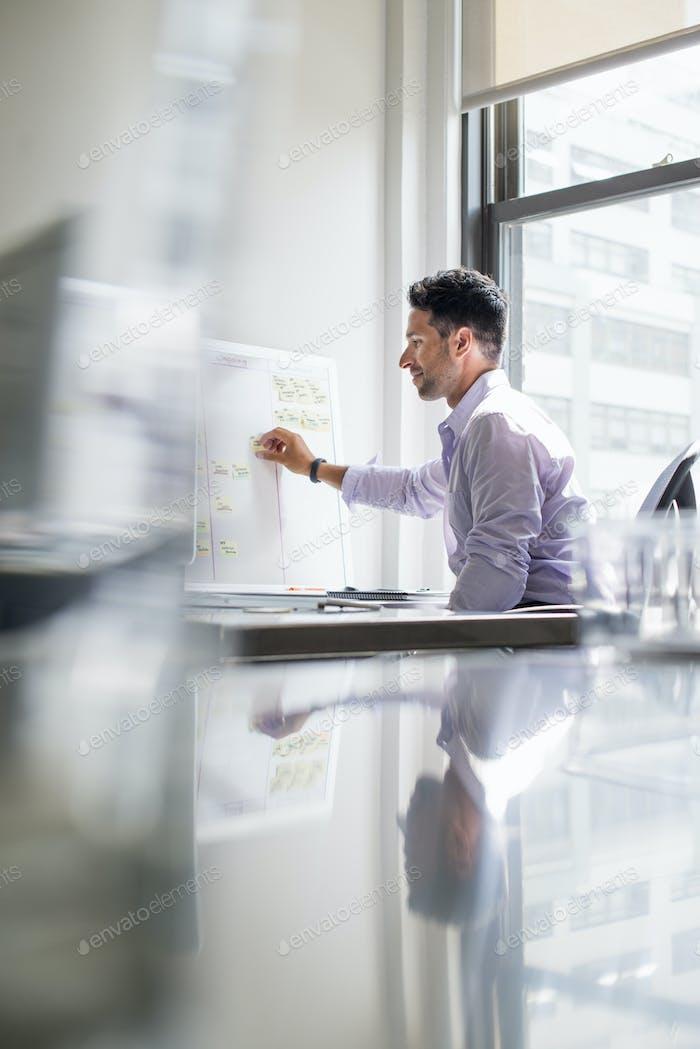 Büroleben. Ein Mann, der an einem Wanddiagramm in seinem Büro arbeitet.
