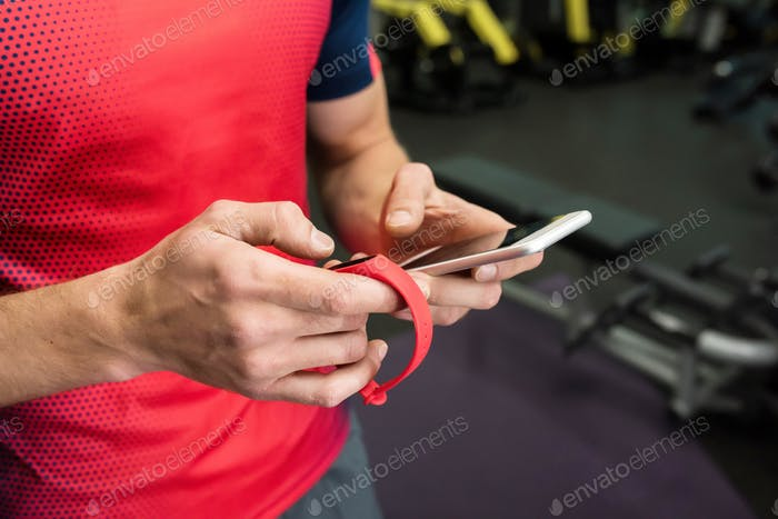 Sportsman using Fitness Device in Gym