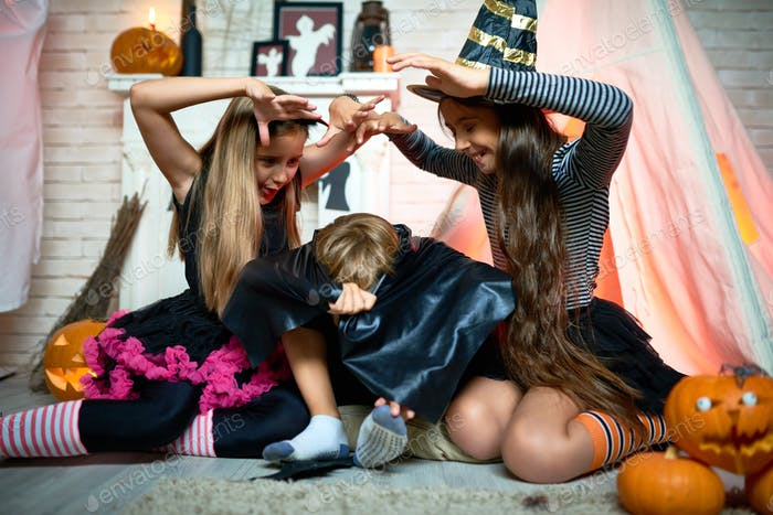 Grimacing girls scaring friend at Halloween party