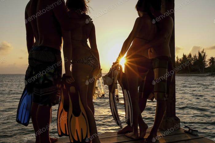 A small group of people, waist down, standing on a jetty with diving gear and flippers looking at