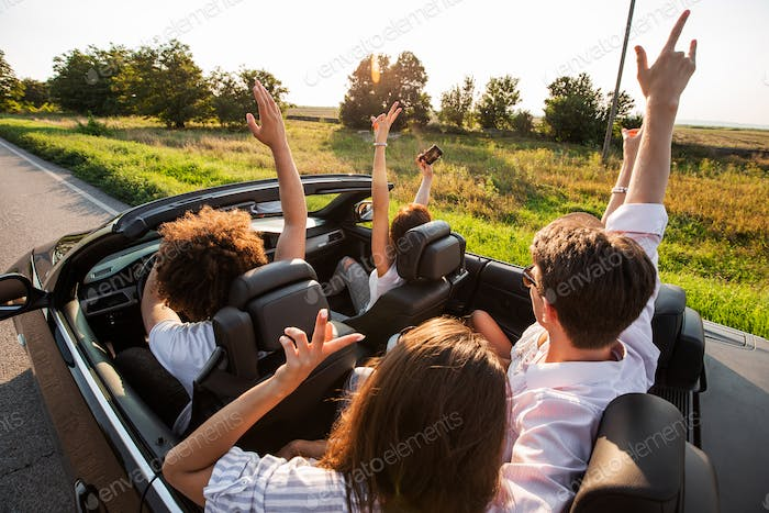 Young girls and guys are sitting in a black cabriolet, holding their hands up and making selfie on a