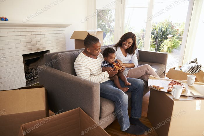 Familie Machen Sie eine Pause auf Sofa mit Pizza On Moving Day