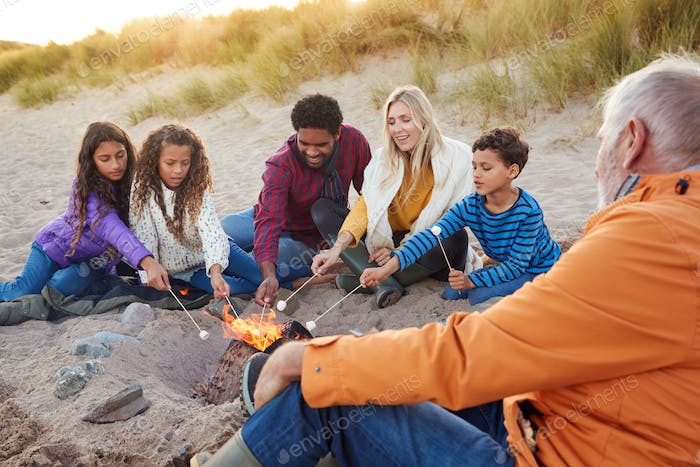 Multi-Generation Family Toasting Marshmallows Around Fire On Winter Beach Vacation