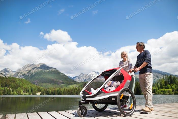 Senior couple with grandchildren in jogging stroller.