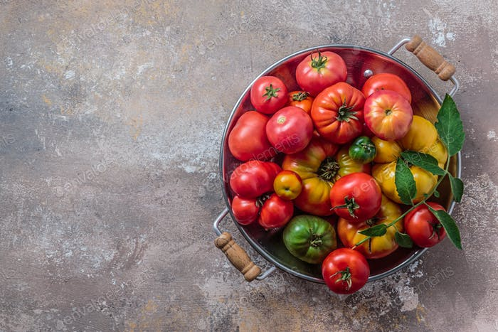 Ripe tomatoes in a pan on stone background, copy space