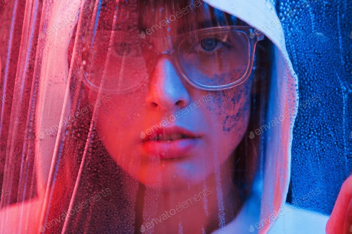 Looking through the wet material. Studio shot in dark studio with neon light. Portrait of young girl