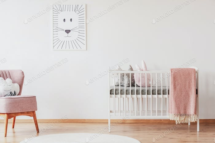 White crib with pillows and pink blanket in cute baby room with