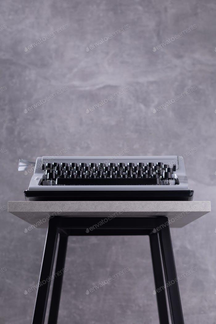 Vintage typewriter at stool or shelf near grey wall background