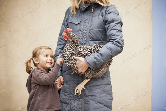A woman holding a chicken and a girl holding her hand