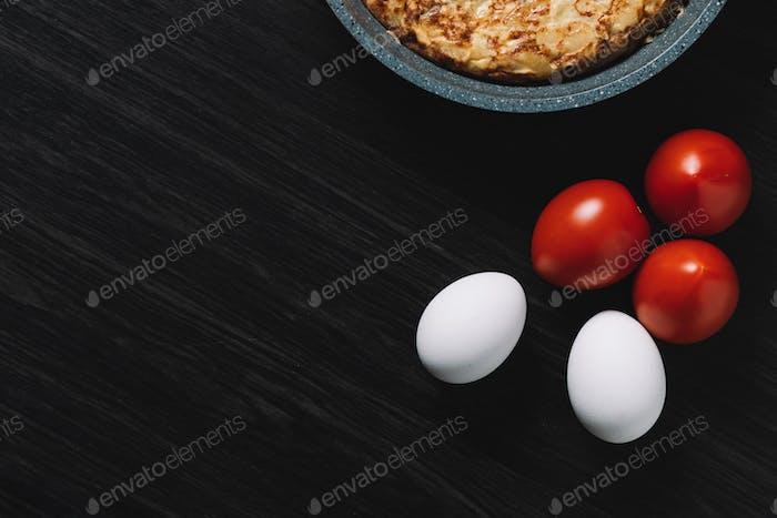 Spanisches Omelett auf Holztisch, mit Eiern und Tomaten