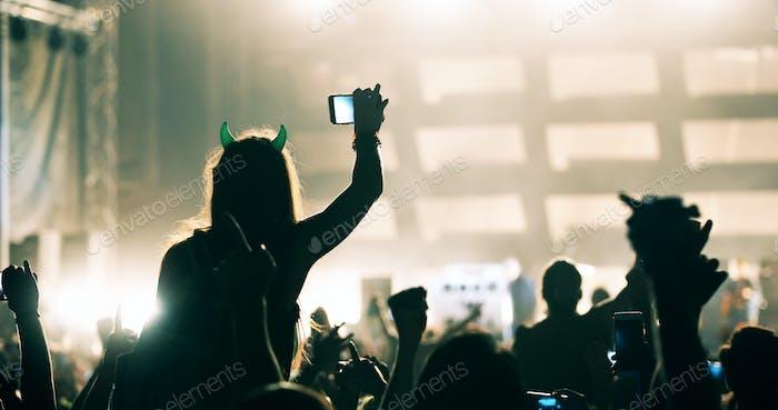 Girl recording video material on music festival