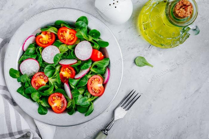 Grüne Salatschüssel mit Tomaten und Rettich.