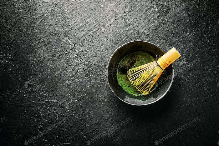 Matcha tea in black bowl on dark