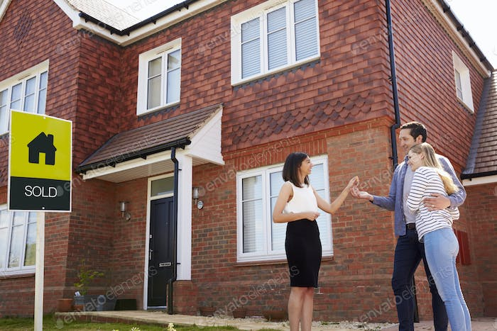 Young Couple Collecting Keys To New Home From Realtor