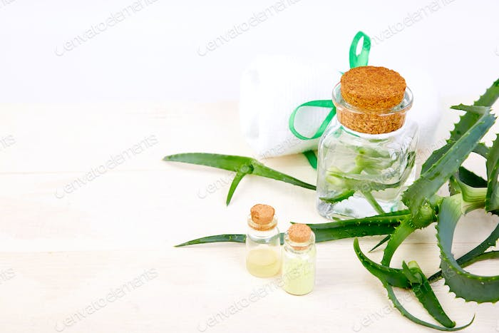 Aloe vera oil in glass bottle and towel for spa
