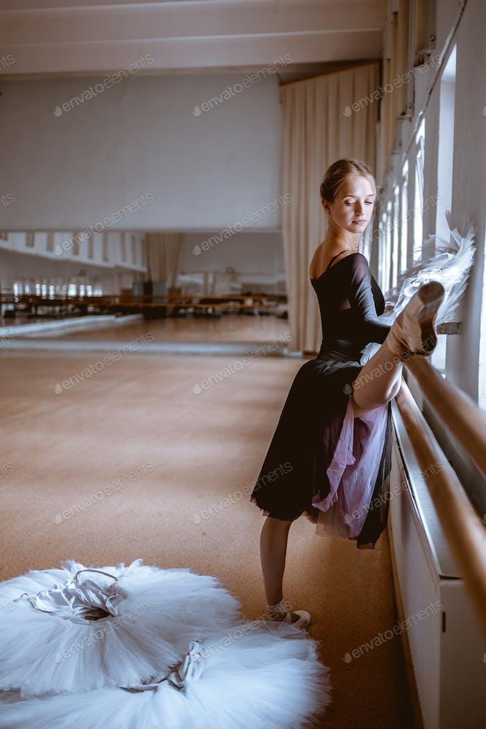 Молодая современная балетная танцовщица позирует на фоне комнаты