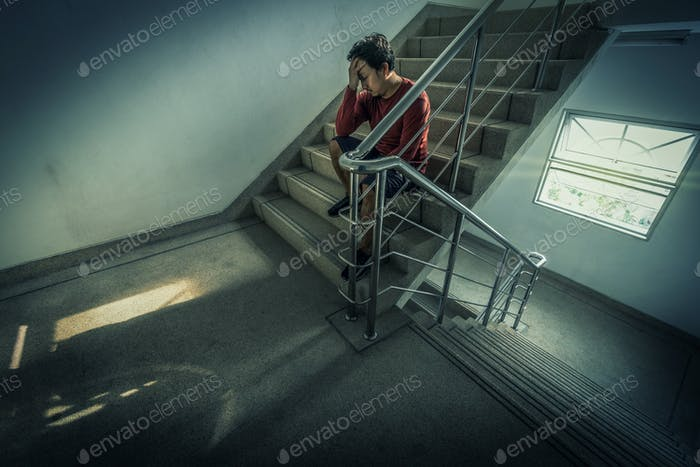 Depressed man sitting head in hands on the staircase in the fire escape or building stair