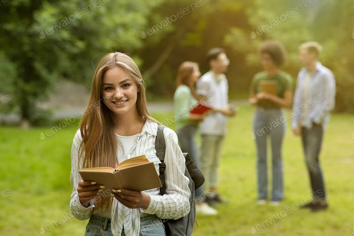 Besutiful college student girl with book posing outdoors with classmates on background