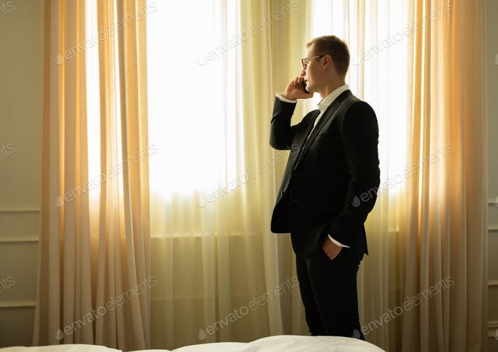 Modern adult businessman calling by phone in hotel