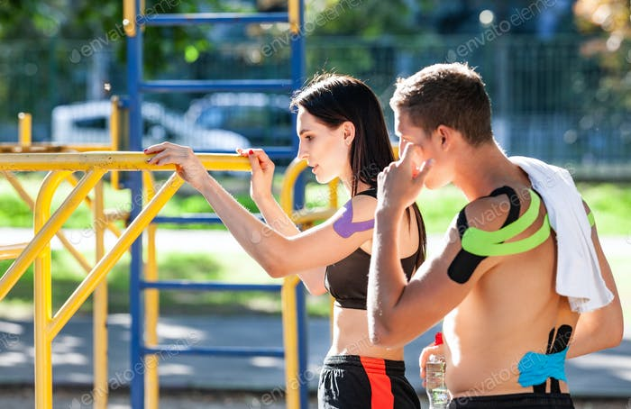 Couple with kinesiological taping training outdoors