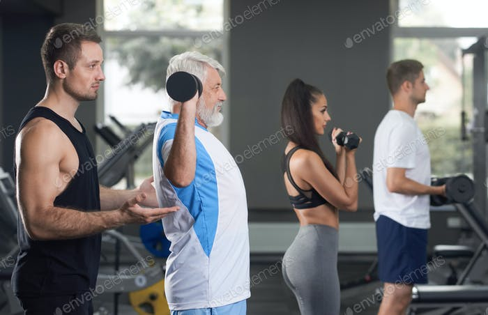 Fit people working out in modern gym with trainer