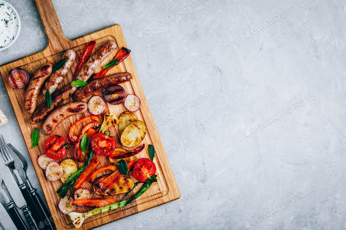 Barbeque food. Grilled sausages and vegetables on  wooden board
