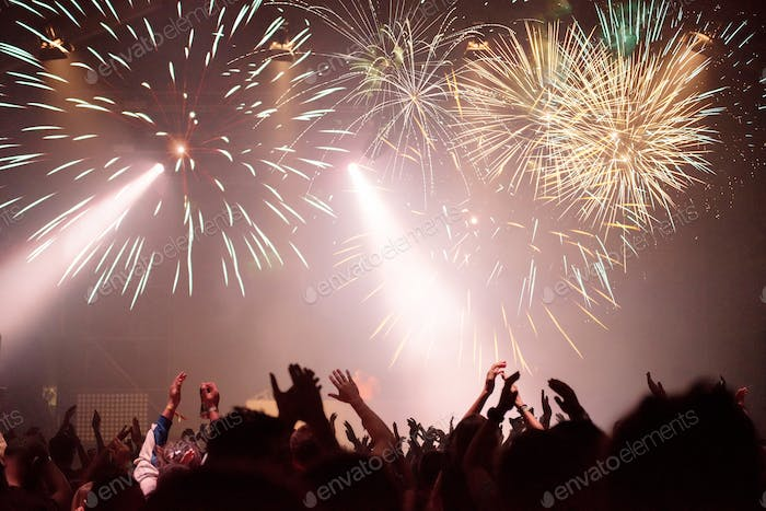 Fireworks and crowd celebrating the New Year. Space for text