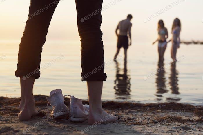 Junger Mann steht am Strand, während junge Frau