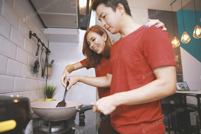 Happy Asian Couple Cooking Together in The Kitchen