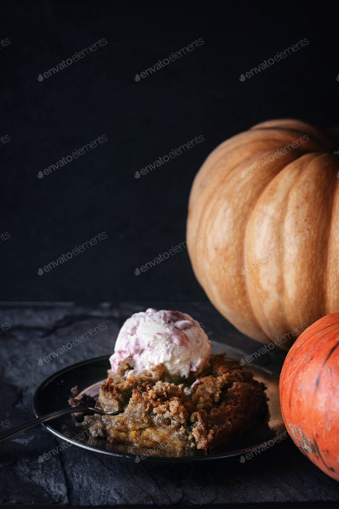 Pumpkin dump cake with ice cream on the stone table vertical