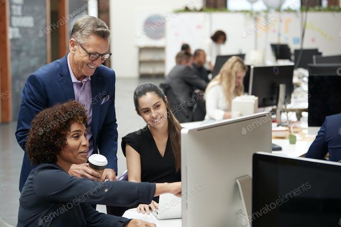 Businessman And Businesswomen Working At Computer On Desk In Open Plan Office