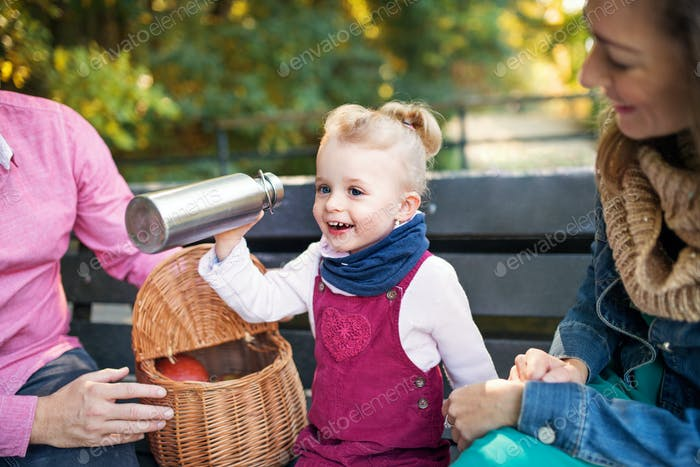 Beautiful young family with small daugther sitting on bench in autumn park