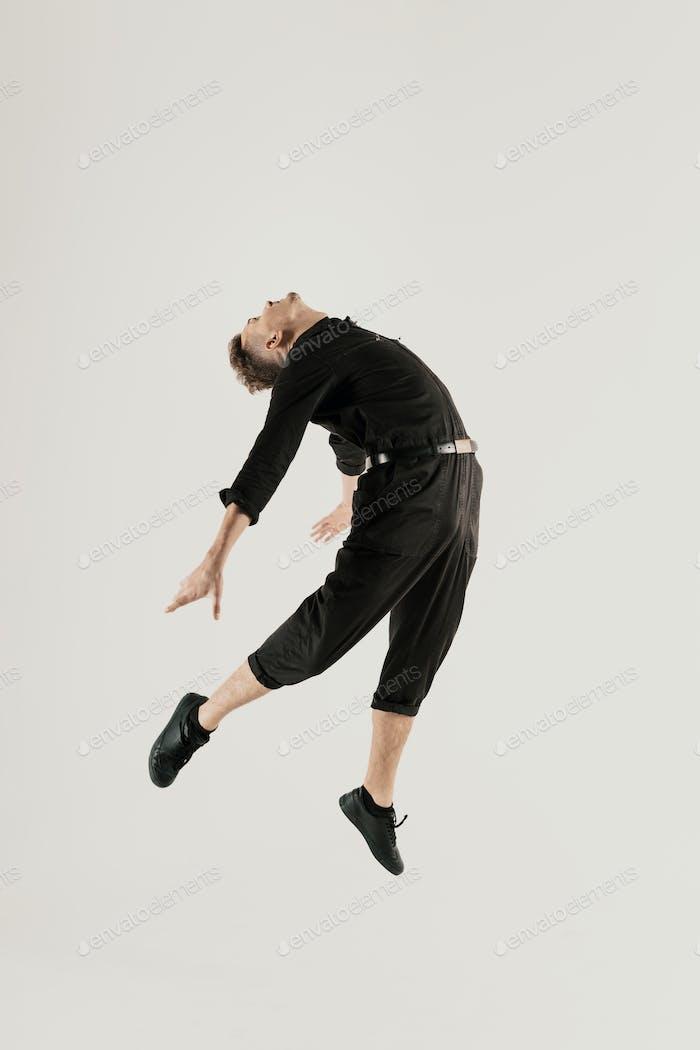 Selbstbewusster Mann springen zu Fuß vor weißem Hintergrund