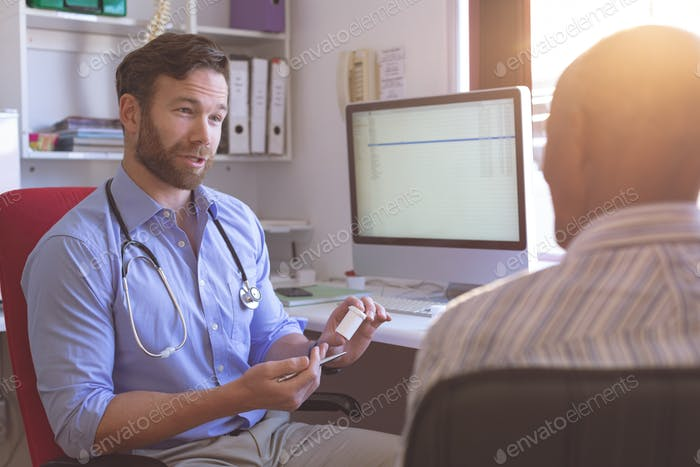 Male doctor and senior man interacting with each other in clinic