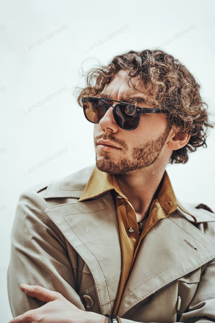 Portrait of a handsome casual guy with curly hair posing in the bright studio and looking questioned