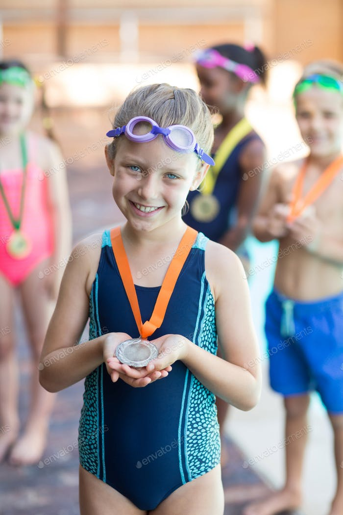 Happy little girl showing medal at poolside