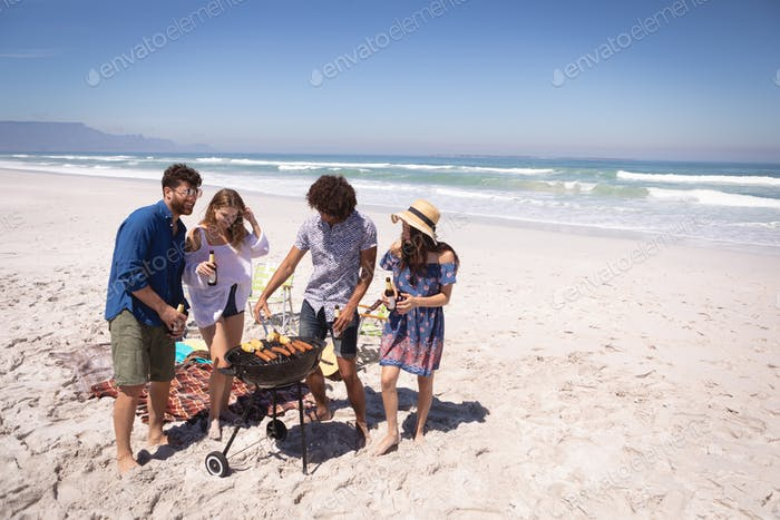 Group friends surrounding of barbecue at beach while they are drinking a beer against ocean waves