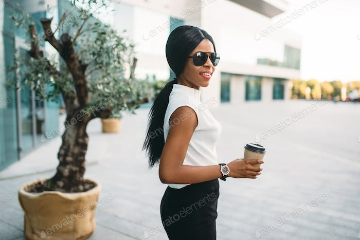 Business woman in sunglasses with coffee outdoors