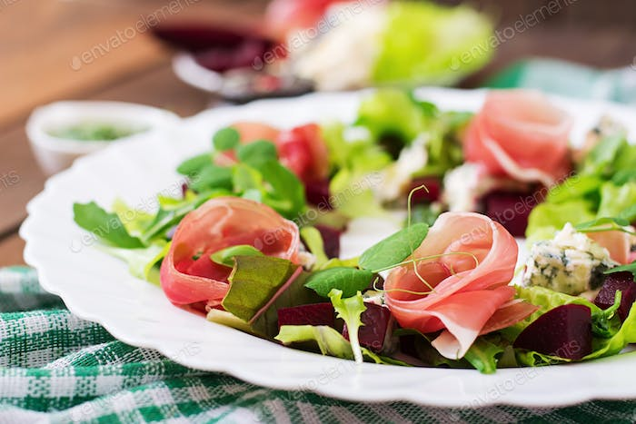 Salad with baked beet, blue cheese, ham and green mix with pesto