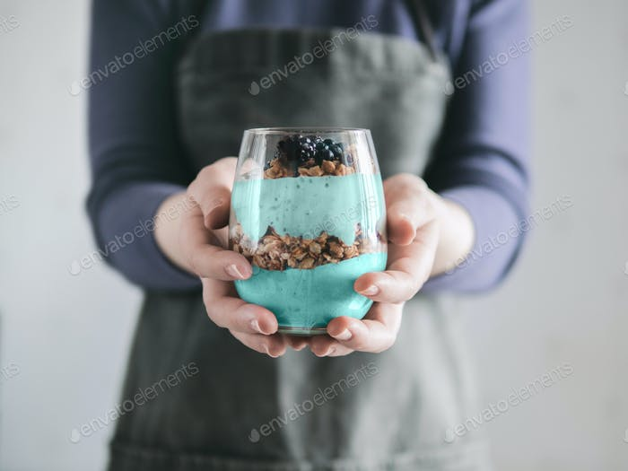 Spirulina smoothie and granola in woman hands