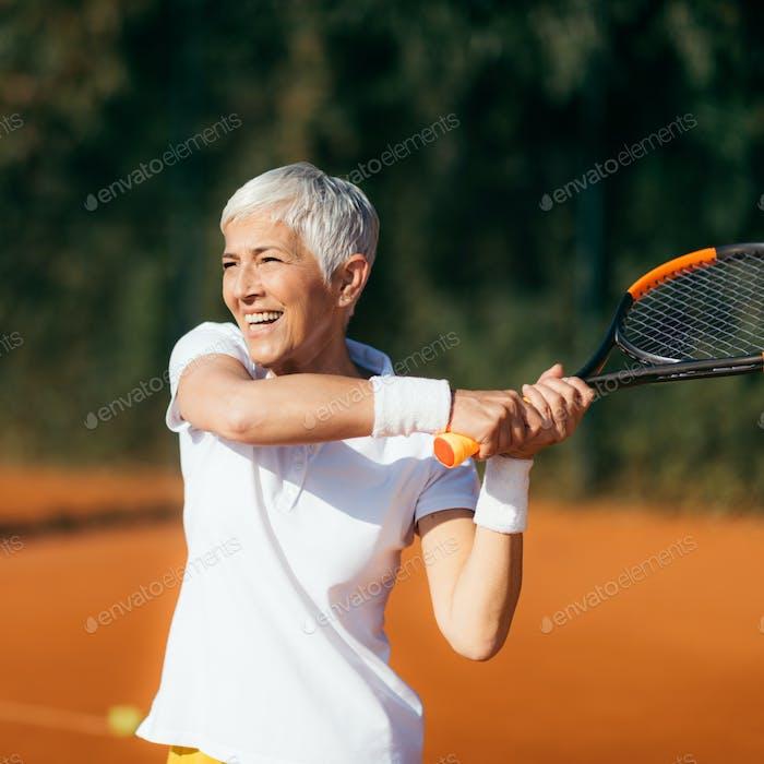 Aktive Lifestyle Senioren — Positive reife Frau Tennis spielen Freizeit